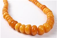 Lot 2507-A butterscotch amber bead necklace, the oval...