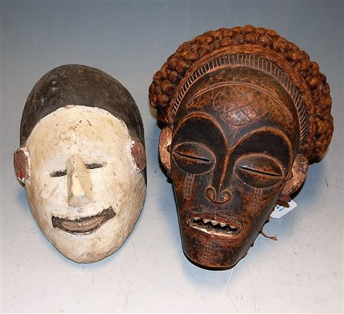 Lot 24-An African carved softwood tribal mask; and one...