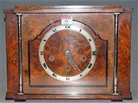 Lot 15-An Art Deco walnut cased mantel clock, having a...