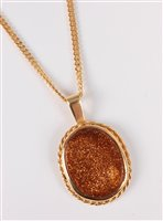 Lot 2505-A goldstone pendant and 18ct chain, the oval...