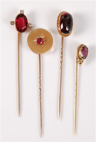 Lot 2506-Four gemset stick pins: to include an oval garnet ...