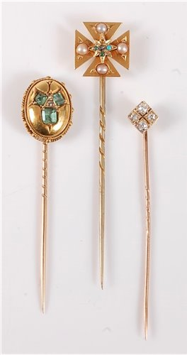 Lot 2508-Three stick pins: to include an oval emerald and...