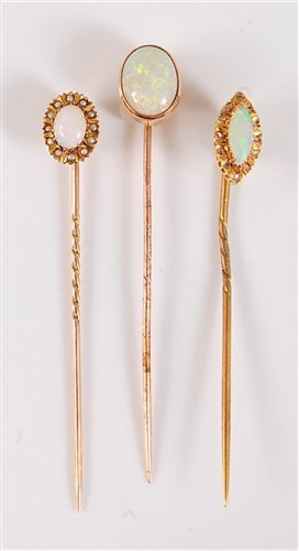 Lot 2510-Three opal stick pins: to include a marquise opal ...