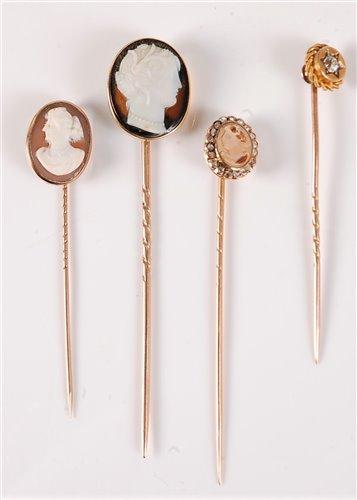 Lot 2531-Three cameo stick pins and a diamond stick pin: a ...