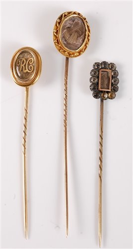 Lot 2533-Three hairwork stick pins: an oval plaited...