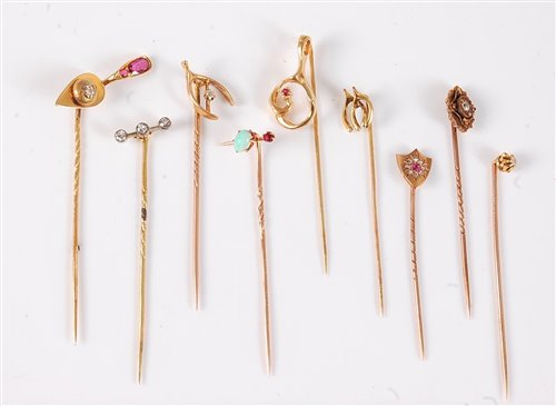 Lot 2538-Nine variously gemset stick pins: a ruby and...