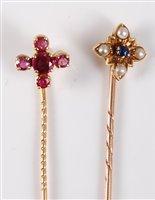 Lot 2540-Two gemset stick pins: a raspberry pink sapphire...