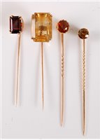Lot 2551-Four gemset stick pins: to include an andalusite...