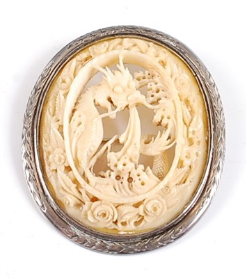 Lot 2503-A white metal oval carved ivory brooch, depicting ...