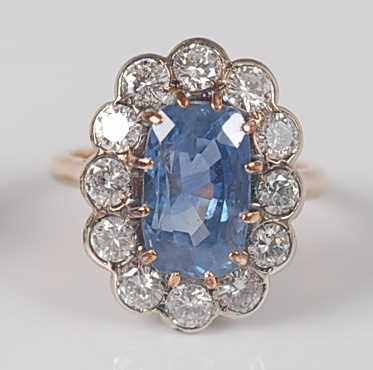 Lot 1174 - A sapphire and diamond oval cluster ring, claw...