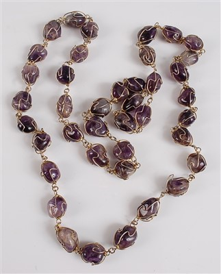 Lot 2521-An opera length amethyst necklace, featuring 40...