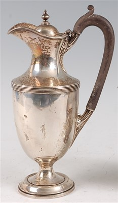Lot 1083 - A George V silver hot water jug, the cover...