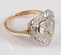 Lot 1226 - An 18ct yellow and white gold heart shaped...