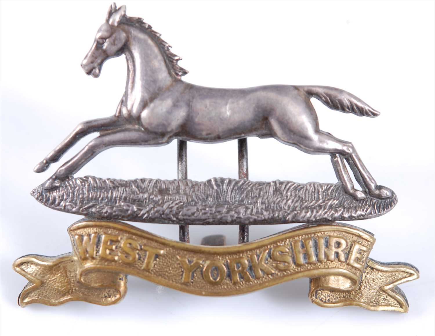 Lot 24-A West Yorkshire Regiment Officer's white metal and gilt cap badge