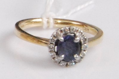 Lot 2048-An 18ct gold, sapphire and diamond cluster ring,...