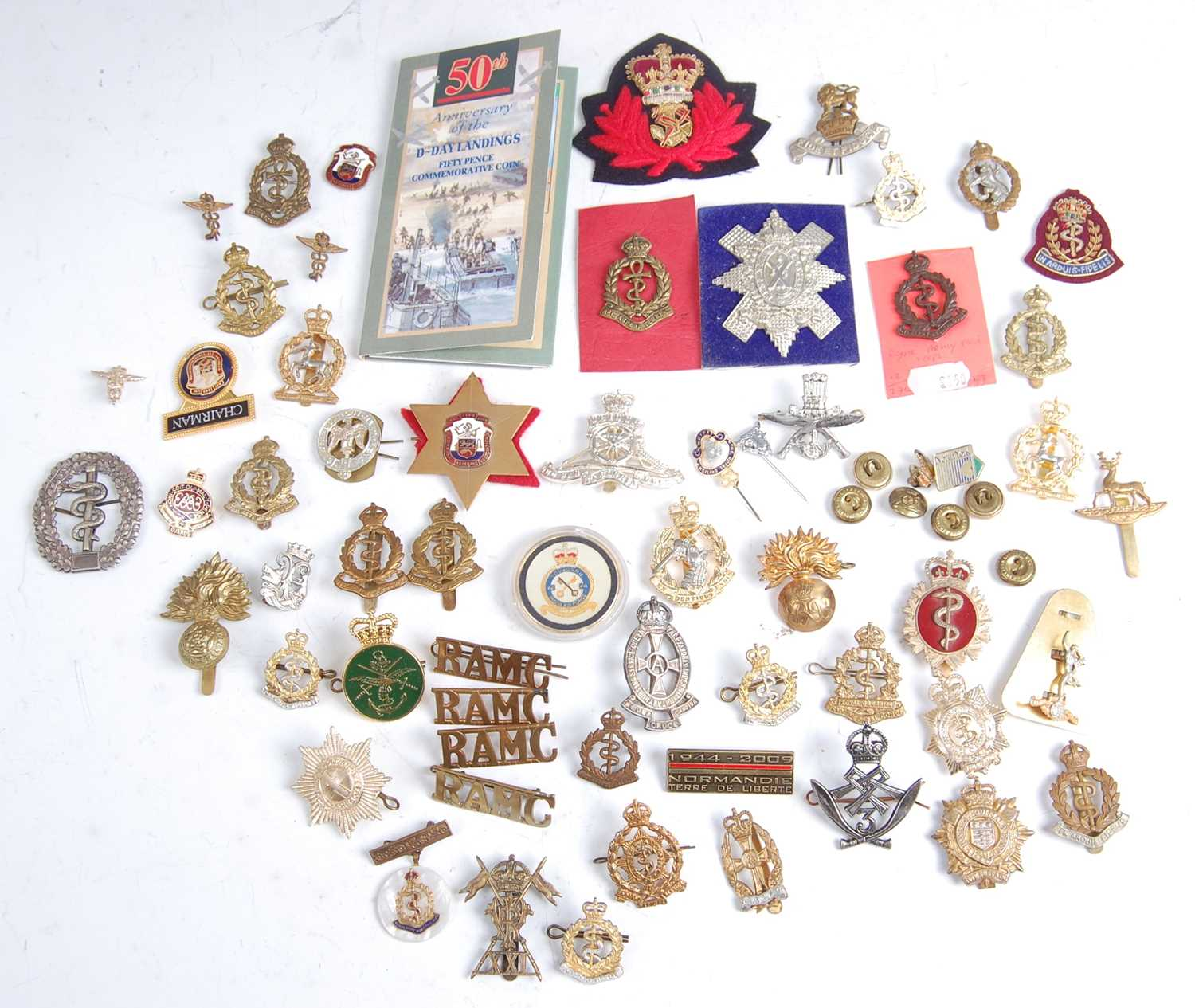 Lot 30-A collection of cap badges, cloth badges, shoulder titles and insignia