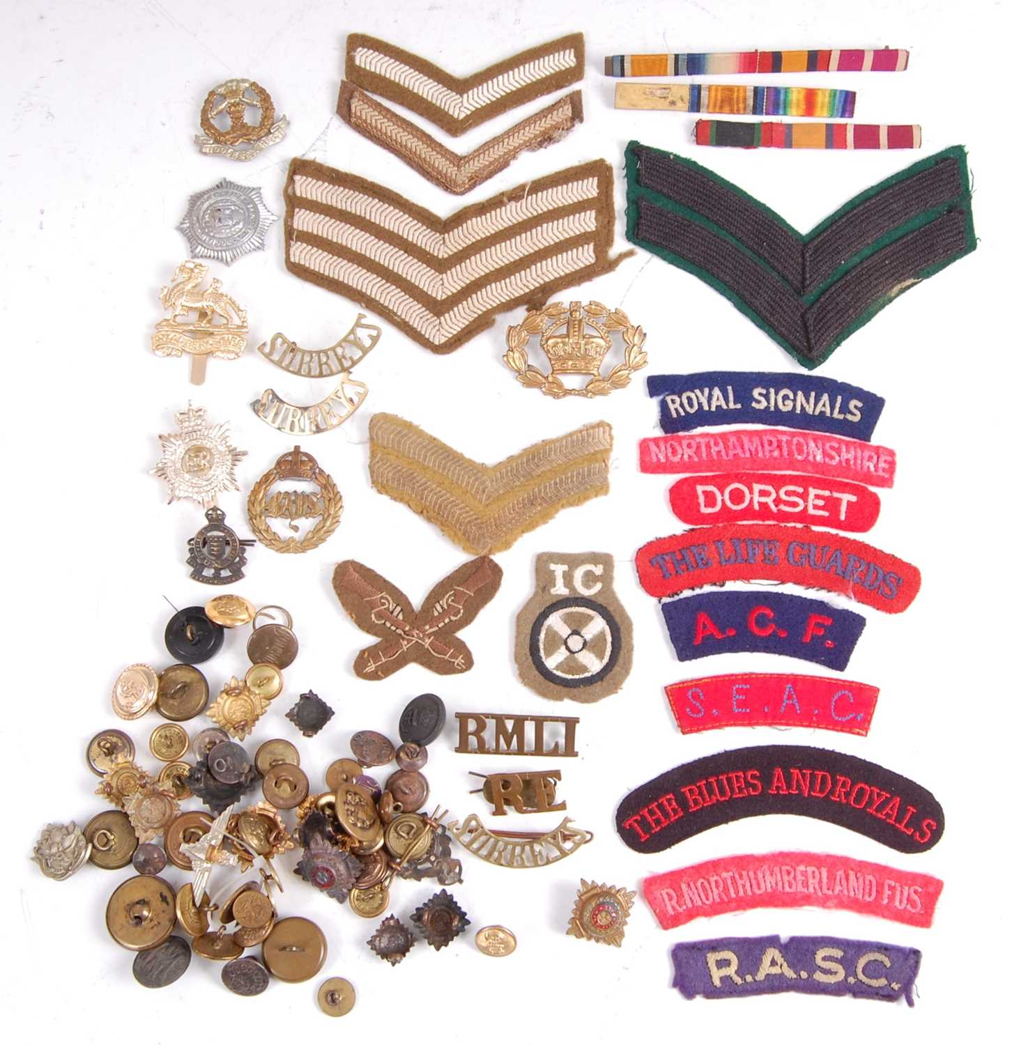 Lot 33-A collection of cap badges, buttons and cloth shoulder titles to include