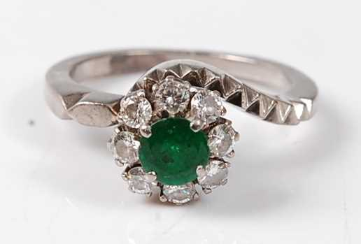 Lot 2504 - A white metal emerald and diamond circular...