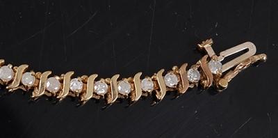 Lot 2513 - A yellow metal diamond line bracelet,...