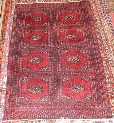 Lot 5 - * An Afghan woollen Baluch rug, the red ground...
