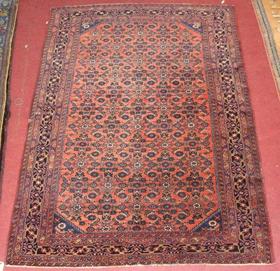Lot 22 - * A Persian woollen rug, the rust coloured...