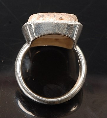 Lot 2576 - A white metal dress ring, featuring a rough...