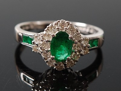 Lot 2616 - A white metal, emerald and diamond oval...