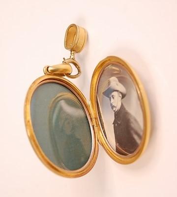 Lot 3086 - A yellow metal oval diamond set locket,...