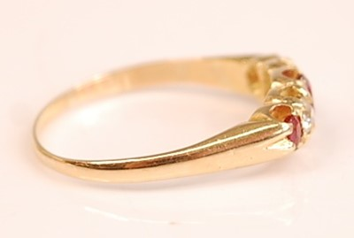Lot 3098 - A yellow metal, ruby and diamond half hoop...