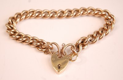 Lot 3085 - A 9ct gold curblink bracelet with heart shaped...