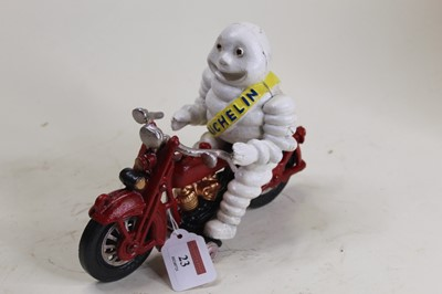 Lot 23 - A cast iron model of the Michelin Man riding a...