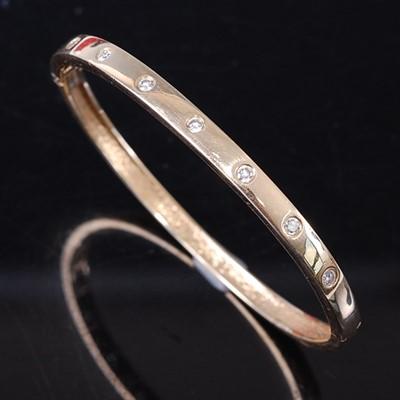 Lot A yellow metal diamond oval hinged bangle,...