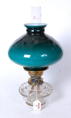 Lot 21 - An early 20th century oil lamp, having a green...
