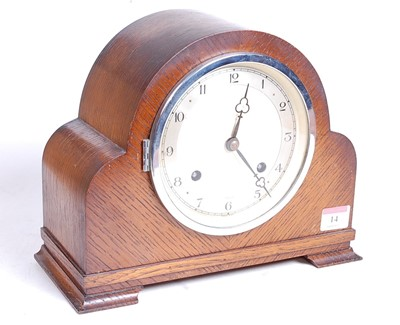 Lot 14 - A 1930s oak cased eight-day mantel clock, the...